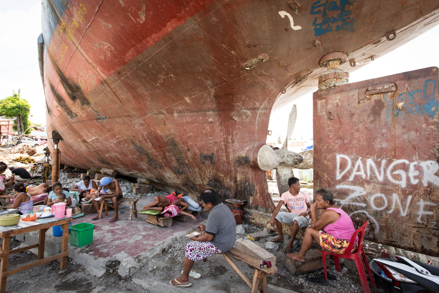 Some locals take shade underneath a boat that was washed onto shore during Thyphoon Yolanda, it was about half a mile in, shows how strong the typhoon was