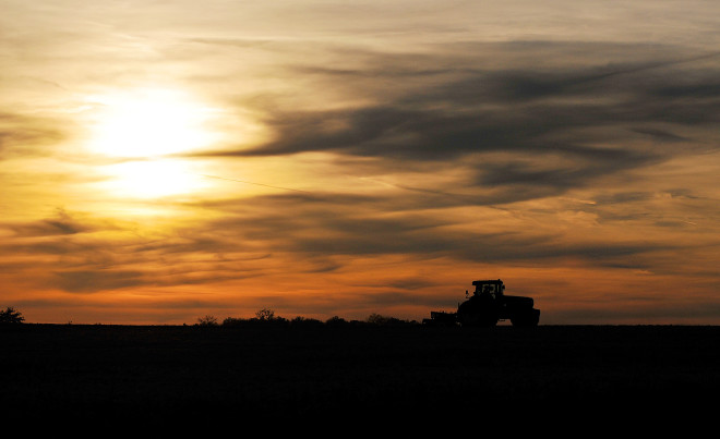 A tractor tills up land off of Ohio 100 as the sun sets.