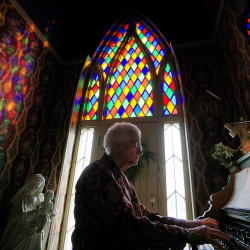 Mansfield resident and volunteer Barbara Piatt plays Christmas tunes on the pump organ in the second floor chapel at Oak Hill Cottage Sunday afternoon.