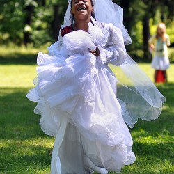 Danajah Anderson, 8, of Mansfield, has a laugh as she runs in the dress-up relay during a picnic to celebrate the end of the Ocie Hill Summer Enrichment Program at North Lake Park.